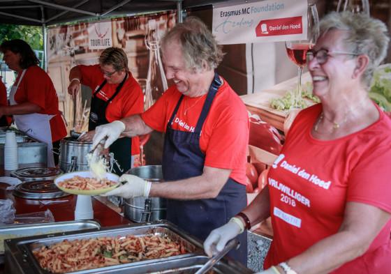 De vrijwilligers serveren de pasta