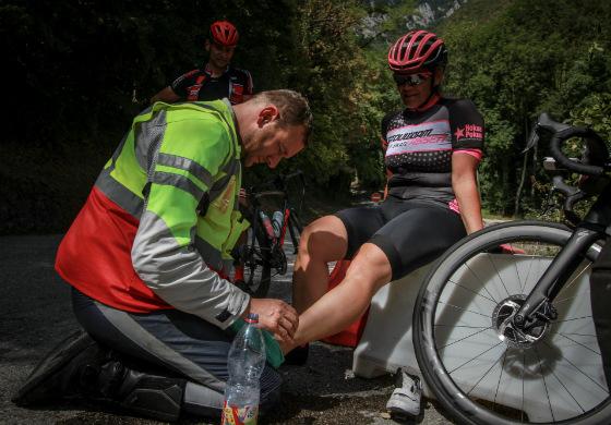 Een motard helpt een wielrenner