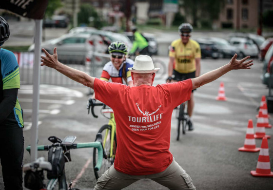 Een vrijwilliger onthaalt enthousiast een deelnemer